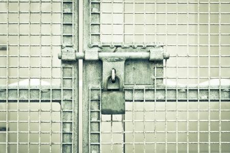 prison bars: A padlocked metal gate in dramatic monochrome