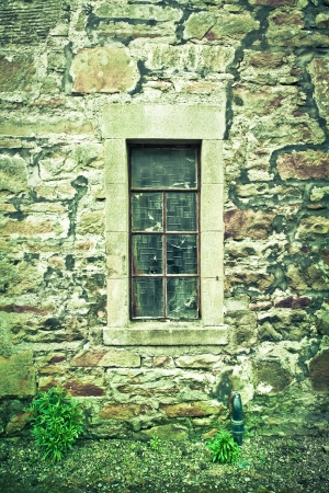 A cracked window in a derelict stone cottage photo