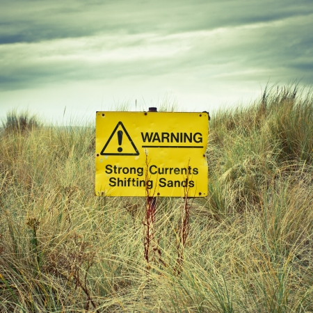 shifting: Warning sign on a british beach on a stormy day