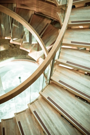stair well: A modern wooden spiral staircase in muted tones Stock Photo