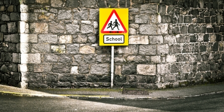 Warning sign for a school on a roadside photo