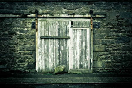 muted: Old weathered wooden door in a wall in muted tones Stock Photo