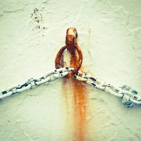 A rusty chain against a white wall in dull vintage tones Stock Photo - 16772158
