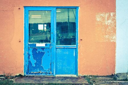 A weathered blue door in an orange wall Stock Photo - 17630808