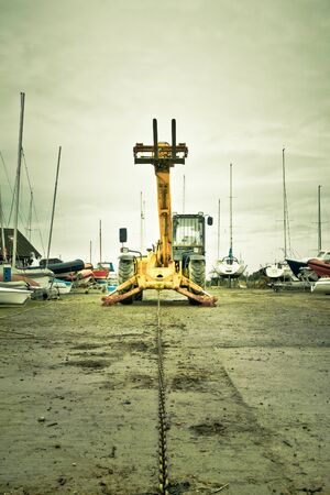 A yellow boat winch with a chain at a boat yard Stock Photo - 17630798