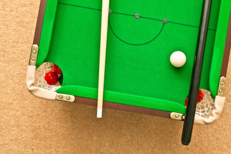 snooker cues: A small pool table on the floor Stock Photo