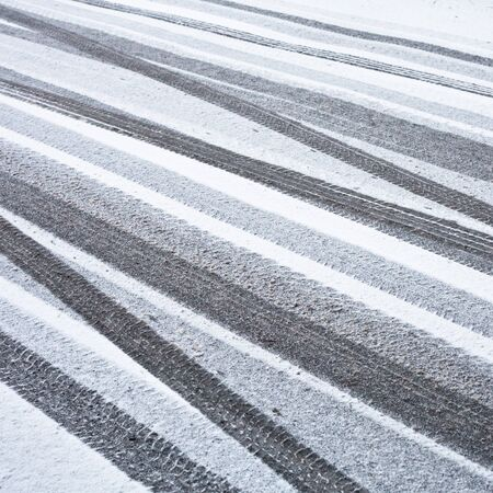 icy conditions: Many tyre trackson a road  in the snow