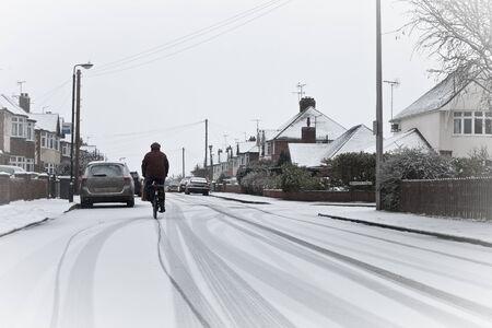 raod: A cyclist on a snowy residential raod in England