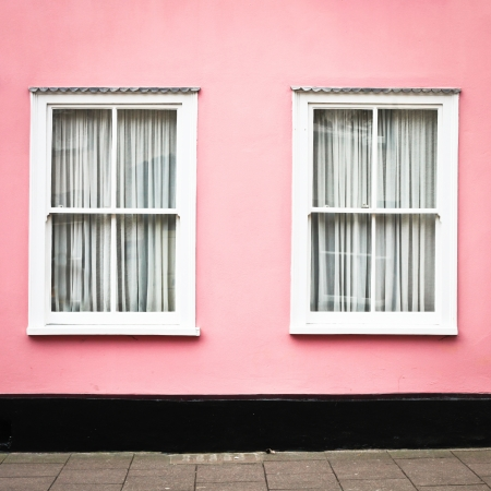 A pink house with white windows in Suffolk, England photo