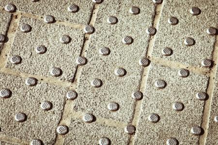 braille: Metallic espárragos en concreto en un paso de peatones Foto de archivo