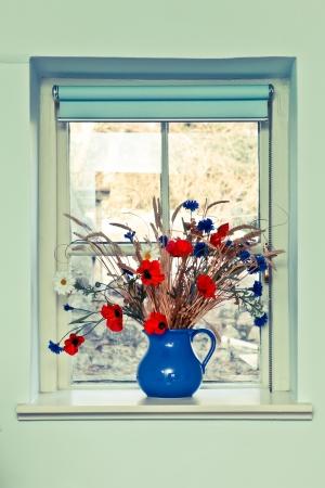 Krug frische Sommerblumen auf der Fensterbank Lizenzfreie Bilder