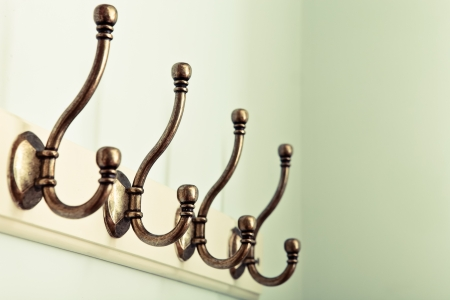 Row of vintage coat hooks on a wooden plaque Stock Photo