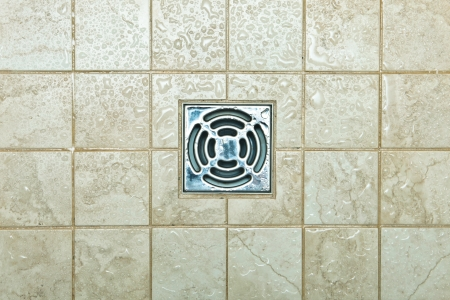 Metal drain hole in the tiled floor of a shower