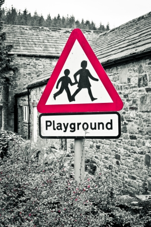 A playground warning sign with selective color desaturation photo