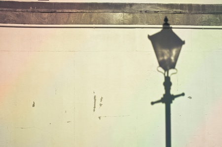 Lamp post shadow cast on a stone wall Stock Photo
