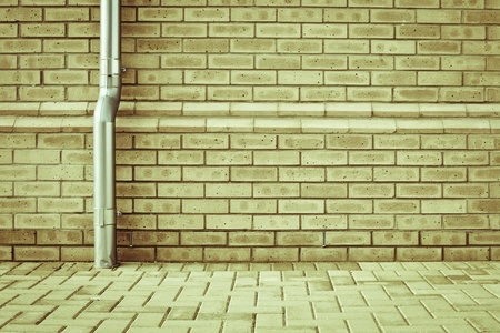 A metal drainpipe against a modern brick wall as a background Stock Photo - 21543462
