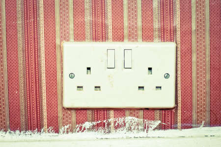 Twin power socket in a wall with retro wallpaper photo
