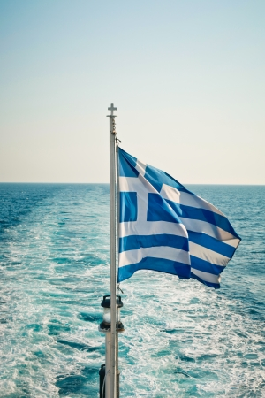 journeying: Greek flag flying on a ferry sailing Stock Photo