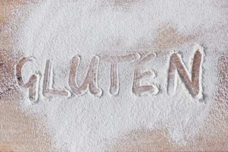 Gluten written in flour on a wooden surface Stock Photo
