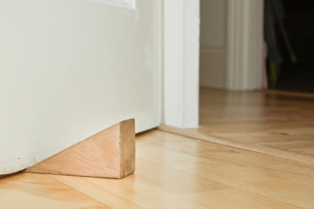 A wooden door stopper on a laminate floor