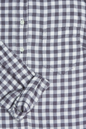 Front of a gingham shirt with a rolled up sleeve photo