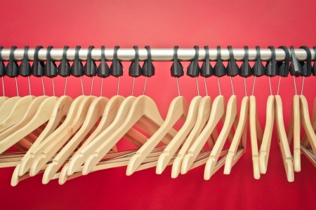Wooden clothes hangers on a rail in front of a red wall