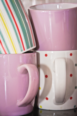 Stack of colorful mugs in a kitchen photo