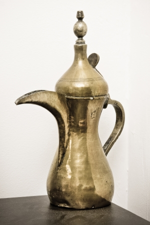 A traditional Omani brass coffee pot on a shelf photo