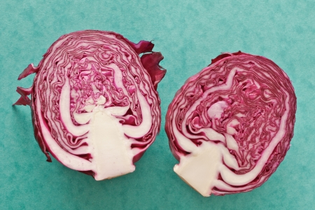 Slices of red cabbage  on a green background photo
