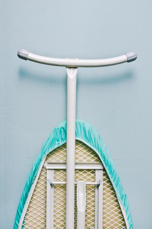 Een strijkplank leunend tegen een blauwe muur