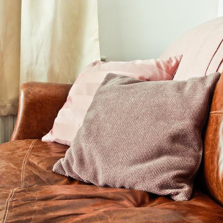 brown leather sofa: Cuscini su un divano in pelle marrone in un salotto