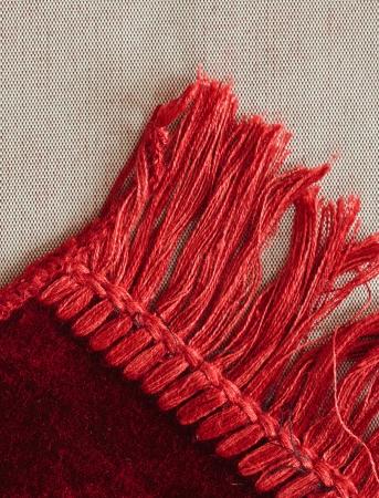 tassles: Corner of a red rug showing tassles
