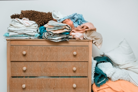 bedroom wall: Piles of bed linen on a wooden chest of drawers
