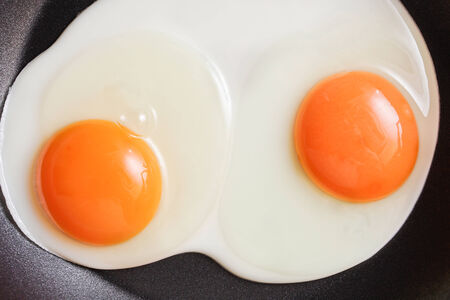 Two fresh eggs being fried in a non-stick pan photo
