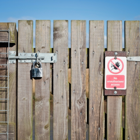 A locked wooden gate with a no access notice photo