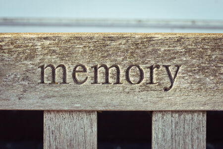 The word memory carved into a wooden bench Standard-Bild