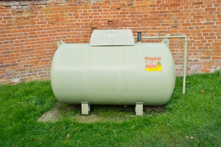 A large propane tank against a red brick wall