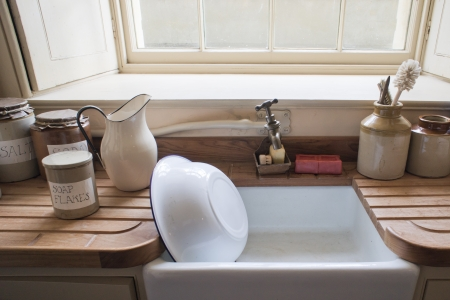 Old fashioned washing up sink with vintage cannisters photo
