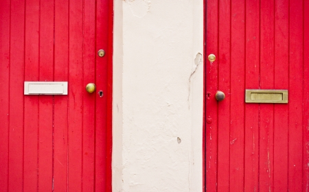 Neighbouring red front doors with letterboxes photo