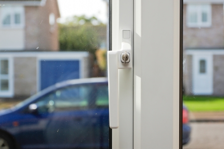Close up of a key in a double glazed window lock with view of neighborhood in background