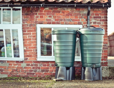 Two water butts collecting rainwater from a gutter