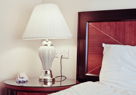 Bedside lamp and table in a hotel bedroom photo