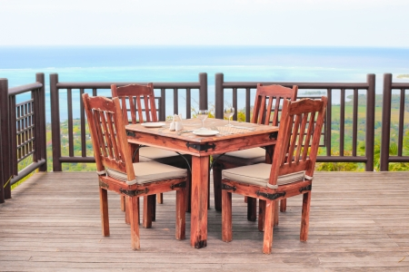 Outside dining table and chairs on a wooden balcony photo