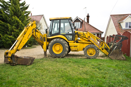 BURY ST EDMUNDS, UK – DECEMBER 30, 2013: A JCB industrial digger in the front yard of a house.