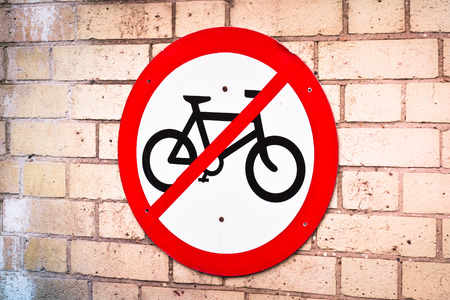 A sign prohibitbng cycling on a brick wall photo