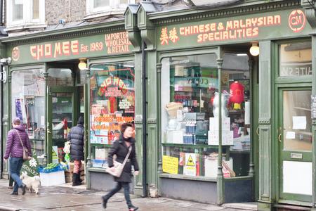 uk cuisine: CAMBRIDGE, UK - JANUARY 25, 2014:  People walking past an oriental food shop in Camrbidge.