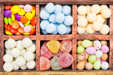 Selection of coloful sweets in a wooden container photo