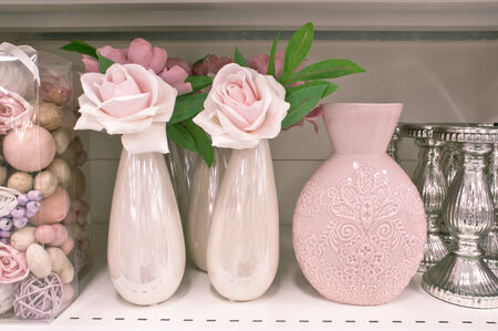 Flower vases and pot pourri on a shelf photo