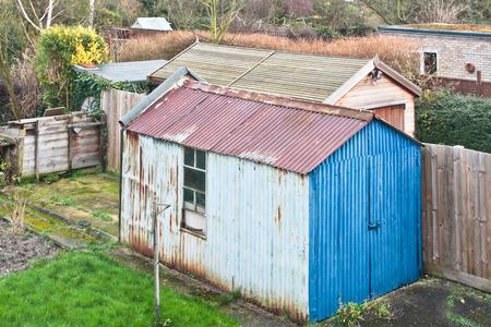 A rusty metal garden shed in an english home