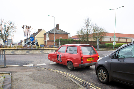 stopped: BURY ST EDMUNDS, UK - MARCH 01, 2014: A 1992 red Reliant Robin at a roundabout in Bury St Edmunds. Editorial